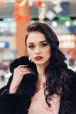 Beautiful girl in a black fur coat. Beauty Fashion Model Girl in Mink Fur Coat. Beautiful Woman in Luxury Brown Fur Jacket . Winter Fashion Stock Photos