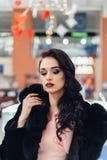 Beautiful girl in a black fur coat. Beauty Fashion Model Girl in Mink Fur Coat. Beautiful Woman in Luxury Brown Fur Jacket . Winter Fashion Stock Image