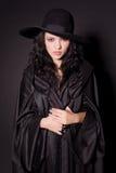 Beautiful girl in black hat. Studio isolated stock image