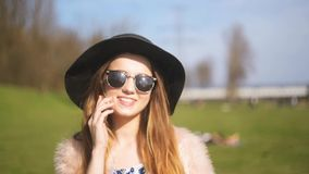 A beautiful girl in a black hat and sunglasses speaks on the phone in the street. The girl in the trip calls , happy and smiling. stock video