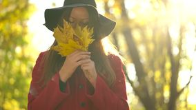 Beautiful girl in black hat walks in the autumn forest and enjoys good weather. Beautiful woman in black hat walks through the autumn forest and enjoys good stock footage