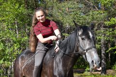 Beautiful girl on black horse Royalty Free Stock Images