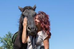 Beautiful girl and black horse in nature. Kiev, Ukraine Stock Photography