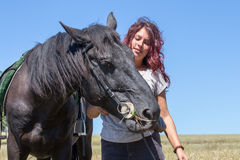 Beautiful girl and black horse in nature. Kiev, Ukraine Royalty Free Stock Photo