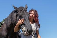 Beautiful girl and black horse in nature. Kiev, Ukraine Royalty Free Stock Photos