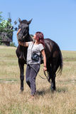 Beautiful girl and black horse in nature. Kiev, Ukraine Royalty Free Stock Photography