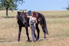 Beautiful girl and black horse in nature. Kiev, Ukraine Stock Image
