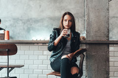 Beautiful girl in a black jacket in a cafe Royalty Free Stock Photo