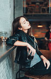 Beautiful girl in a black jacket in a cafe Stock Photo