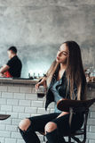 Beautiful girl in a black jacket in a cafe Stock Image