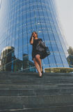 Beautiful girl in black jacket in his hands coming down the steps of the business center Royalty Free Stock Images