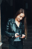 Beautiful girl in black jacket with smartphone Royalty Free Stock Photo