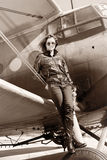 Beautiful girl in black jacket standing on a war aircraft. Stock Photo