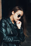 Beautiful girl in a black jacket and sunglasses Stock Photos