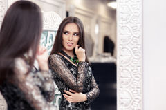 Beautiful Girl in Black Lace Dress Looking in the Mirror Royalty Free Stock Images