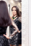 Beautiful Girl in Black Lace Dress Looking in the Mirror Royalty Free Stock Photography
