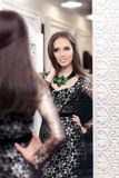 Beautiful Girl in Black Lace Dress Looking in the Mirror Royalty Free Stock Photos