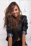 Beautiful girl in black leather jacket looking up and smiling at the camera. White brick wall, not isolated Stock Image