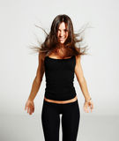 Beautiful girl in black leggings and a t-shirt, tossed hair, smi Stock Image