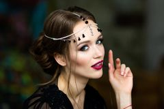 Beautiful girl in a black negligee. Brunette with bright makeup Royalty Free Stock Image