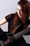 Beautiful girl in black plays bass guitar Stock Photos