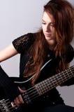 Beautiful girl in black plays bass guitar stock photos
