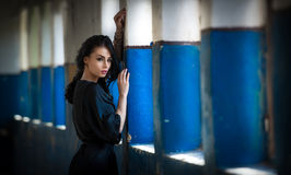 Beautiful girl in black posing in an old hall with columns blue painted. Attractive long hair brunette, side view against wall Stock Photo
