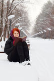 Beautiful girl in black sits on bench with book outdoor Royalty Free Stock Photo
