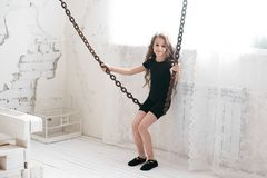 Beautiful girl. Black suit. Chains. Light background. Brown hair. Happy smile Stock Images
