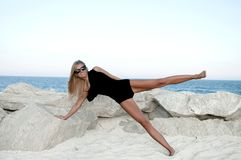 Beautiful woman in black swimsuit on the beach. Fitness Royalty Free Stock Photos