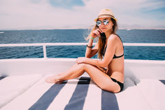 Beautiful girl in a black swimsuit sunning on a yacht in the open sea on a sunny day stock photos