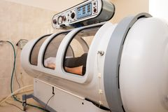 Girl in a black T-shirt and white pants lies in a hyperbaric chamber stock image