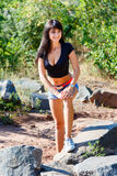 Beautiful girl in a black top and denim shorts standing on a roc. Beautiful brunette girl in a black top and denim shorts standing on a rocks Stock Photo