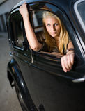 Beautiful girl in a black vintage car. Beautiful young blond girl looking out the window of a black vintage car royalty free stock photos
