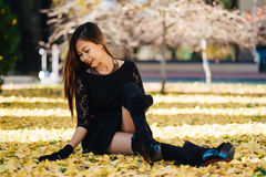 Beautiful girl in black vintage dress and hand glove. Woman in retro dress playing in the park with ginko leafs. Red lips Stock Photo