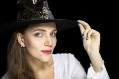 Beautiful girl in black wizard hat stock photography