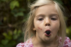 Beautiful Girl with Blackberry in the Garden. Stock Photo