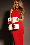 Beautiful girl with blond curly hair and bright evening makeup, wears elegant dress Stock Photos