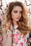 Beautiful girl with blond hair in elegant clothes posing in blooming peach garden. Fashion outdoor photo of beautiful sensual girl with blond hair in elegant royalty free stock photo