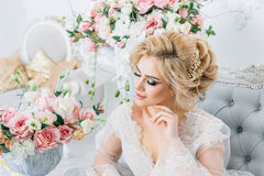Beautiful girl with blond hair in a peignoir elegantly sits on the couch surrounded by flowers. Portrait of a bride in a peignoir sitting on the couch with a Royalty Free Stock Photos