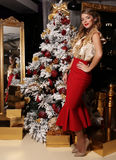 Beautiful girl with blond hair ,posing beside Christmas tree Stock Photos