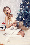 Beautiful girl with blond hair posing beside a Christmas tree Royalty Free Stock Image