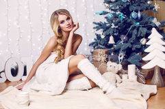 Beautiful girl with blond hair posing beside a Christmas tree Stock Image