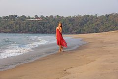 A beautiful girl with blond hair, in a red dress, walks along the seashore and smiles. Summer girl on the sea. Tenderness, alone royalty free stock photography