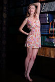 Beautiful girl with blond hair in short dress standing. Next to shelves of books stock photo