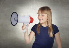 Beautiful girl with blond hair shouting on megaphone. And a gray background Royalty Free Stock Photo