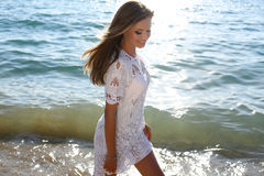 Beautiful girl with blond hair wears elegant lace dress. Fashion outdoor photo of beautiful sexy girl with blond hair wears elegant dress posing on summer beach Royalty Free Stock Image