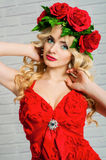 Beautiful girl with blond long hair in a red dress and a wreath Stock Photos