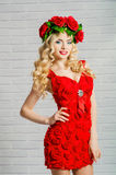 Beautiful girl with blond long hair in a red dress and a wreath Royalty Free Stock Photography