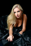 Beautiful girl the blonde on a black bed Stock Photography
